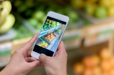 Unrecognisable person using a food app on a cell phone at the supermarket for social media - organic or healthy eating trend concepts